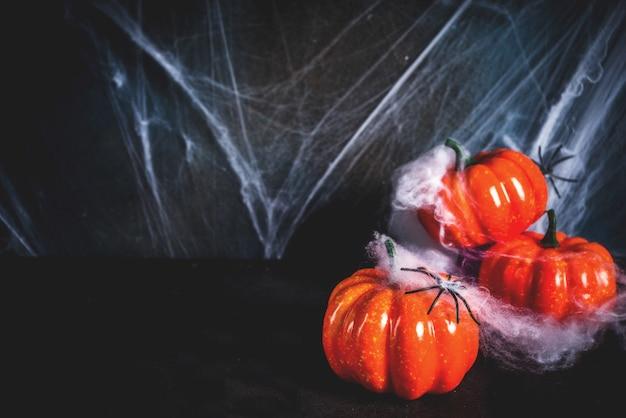 Conceito de halloween, uma parede velha de fundo escuro com teias de aranha e abóboras, fundo de cartão