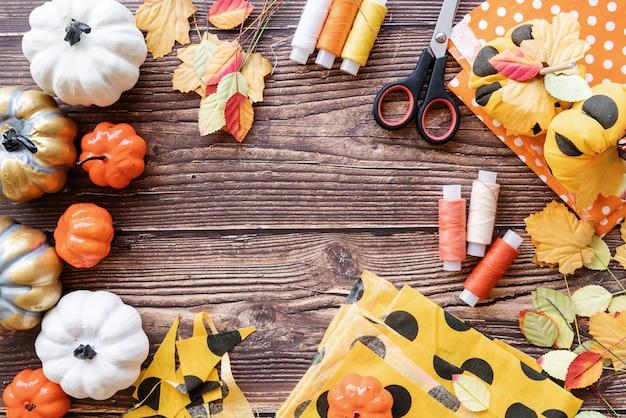 Conceito de halloween. vista superior das decorações de halloween e itens de costura que fazem artesanato de abóbora têxtil com espaço de cópia sobre o fundo de madeira