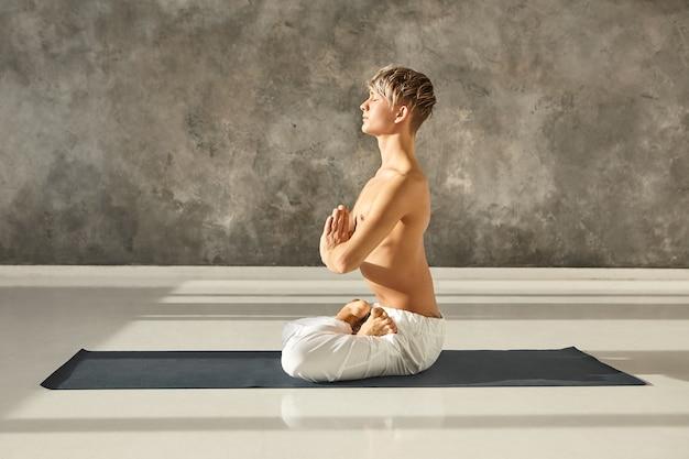 Conceito de hatha ioga, zen, espiritualidade, meditação e relaxamento. retrato de um jovem iogue masculino concentrado e tranquilo, sentado sem camisa no tapete com as mãos em namaste, meditando na postura de lótus