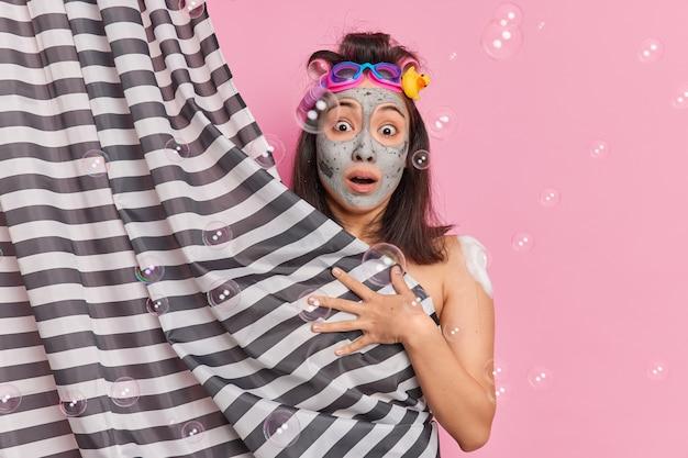 Conceito de higiene e frescor. mulher asiática surpreendida usa rolos de cabelo e aplica máscara de argila nutritiva no rosto, se esconde atrás da cortina do chuveiro aprecia as rotinas matinais