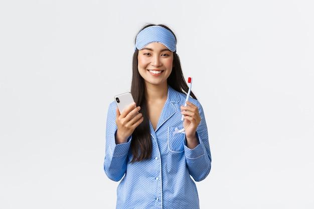 Conceito de higiene, estilo de vida e pessoas em casa. sorrindo linda garota asiática de pijama azul e máscara de dormir, escovando os dentes antes de dormir e usando o smartphone, mostrando os dentes brancos, fundo branco.