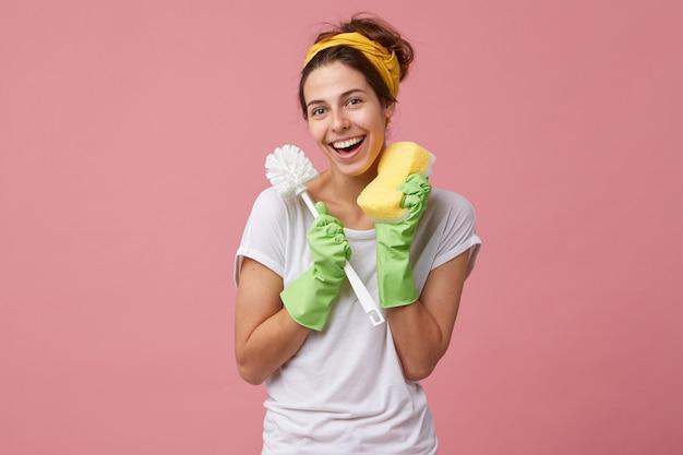 Conceito de higiene, limpeza, limpeza, trabalho doméstico e limpeza. retrato de uma jovem dona de casa caucasiana vestida de maneira casual segurando uma escova e uma esponja de banheiro enquanto faz as tarefas domésticas