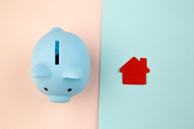 Conceito de hipoteca. casinha de papel ao lado de um cofrinho.