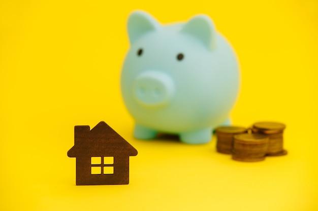 Conceito de hipoteca. cofrinho e moedas próximas. compra de casa.