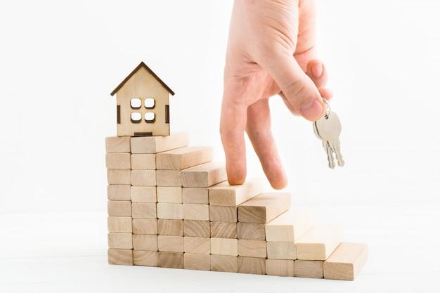 Conceito de hipoteca com mão masculino com chaves subindo escadas de madeira. finalidade do homem na escada da carreira.