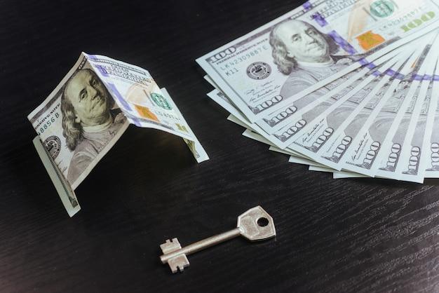Conceito de hipoteca, investimento, imobiliário e propriedade. dinheiro em dólares e chaves de casa