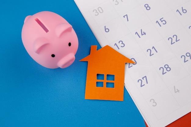 Conceito de hipoteca, lembrete de cronograma de hipoteca ou dia de pagamento imobiliário. cofrinho e mini casa próximo calendário.