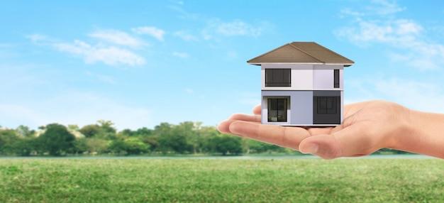 Conceito de hipoteca por casa do dinheiro. segurando o modelo da casa na mão