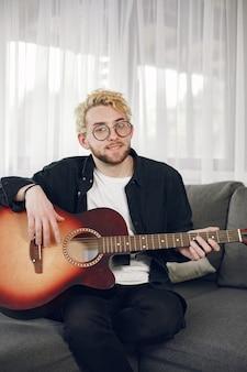 Conceito de hobbies. músico de óculos. tocando violão em casa.
