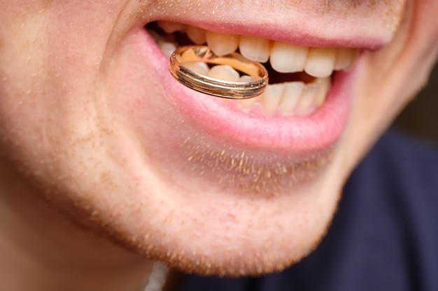 Conceito de homem henpecked segurando uma aliança nos dentes.