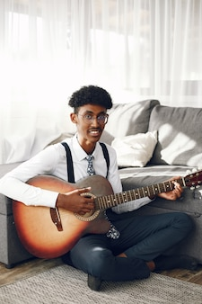 Conceito de hoobies. jovem indiano de meia-calça sentado na sala de estar. músico tocando violão.