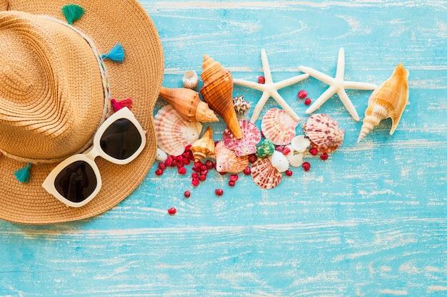 Conceito de horário de verão com conchas do mar, estrela do mar, chapéu e óculos de sol em uma mesa de madeira azul