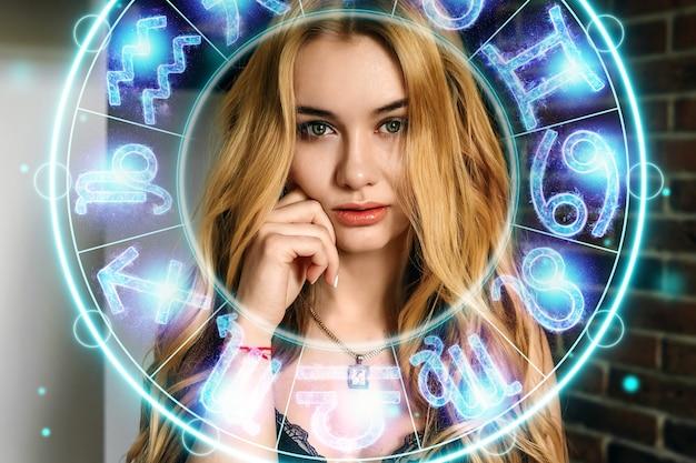 Conceito de horóscopo, retrato de uma linda garota em um fundo de um círculo com os signos do zodíaco, a astrologia.