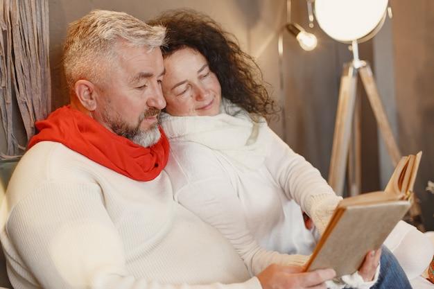 Conceito de idade e pessoas. casal de idosos em casa. mulher com uma camisola de malha branca.