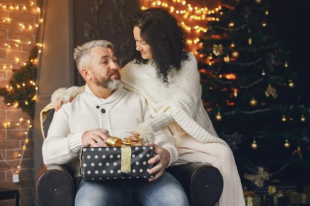 Conceito de idade e pessoas. casal sênior com caixa de presente sobre fundo de luzes. mulher em um moletom de malha branca.