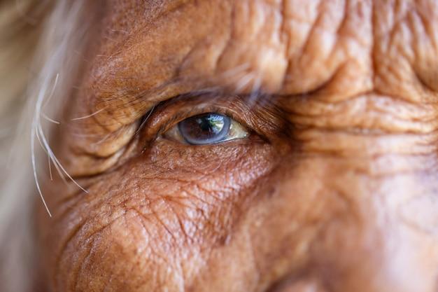Conceito de idade, visão e idosos - close-up do rosto de mulher asiática sênior e olho
