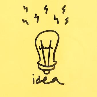Conceito de idéia com lâmpada de mão desenhada em fundo amarelo