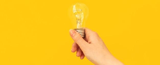 Conceito de ideia de banner, mão de mulher com lâmpada em fundo laranja e amarelo, foto isolada e cópia do espaço