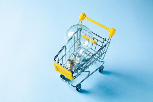 Conceito de ideia de compra. lâmpada em uma cesta em uma superfície azul