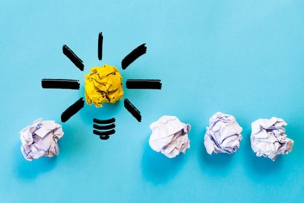 Conceito de idéia de inspiração. lâmpada com papel colorido amassado sobre fundo azul.