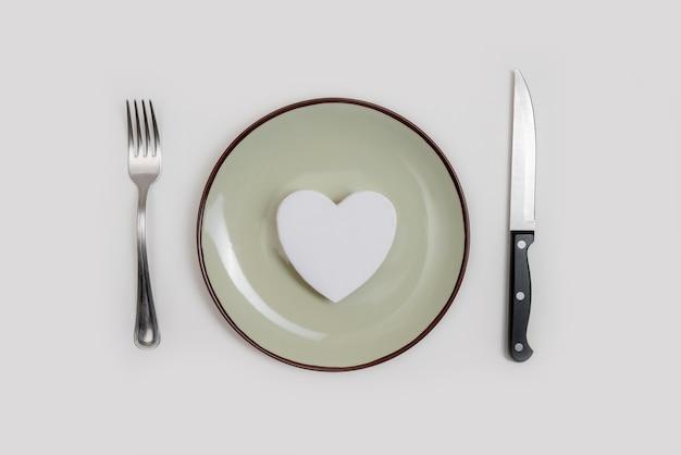 Conceito de ideia de jantar romântico dia dos namorados. coração na placa e desgaste de prata em fundo branco.