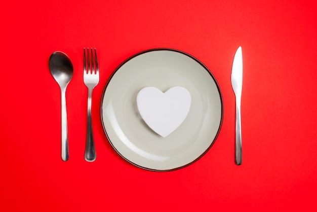 Conceito de ideia de jantar romântico dia dos namorados. coração na placa e desgaste de prata sobre fundo vermelho.