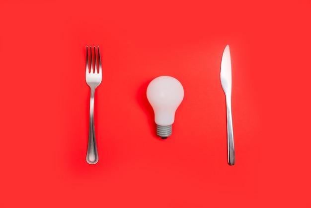 Conceito de ideia de jantar romântico dia dos namorados. lâmpada na placa e desgaste de prata sobre fundo vermelho.