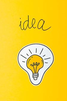 Conceito de idéia de lâmpada em fundo amarelo