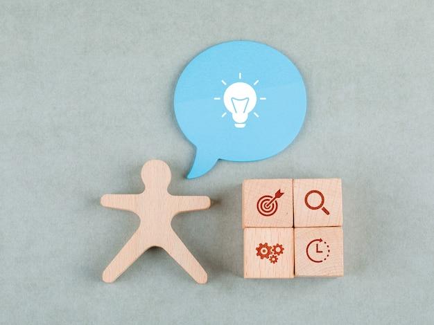 Conceito de ideia de negócio com blocos de madeira com ícone, bolha de mensagem e vista superior da figura humana de madeira.