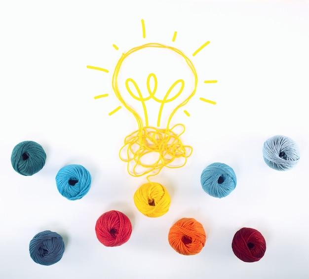 Conceito de ideia e inovação com emaranhado de fios de lã que dá forma a uma lâmpada