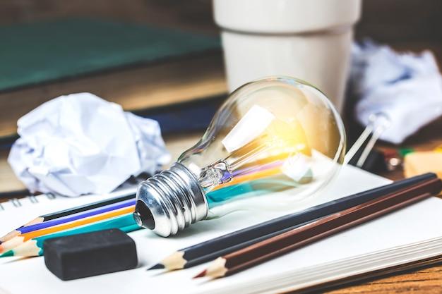 Conceito de ideia excelente com papel de escritório amassado e lâmpada em pé na mesa