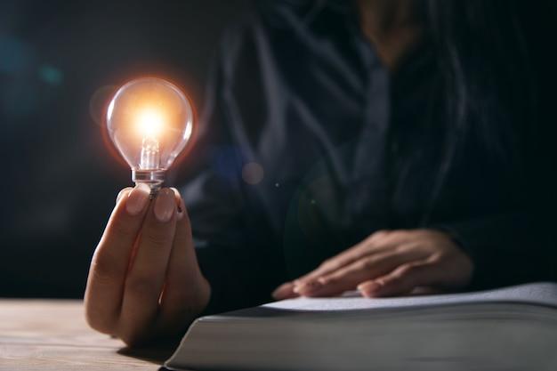 Conceito de ideia, mulher segurando uma lâmpada de um livro