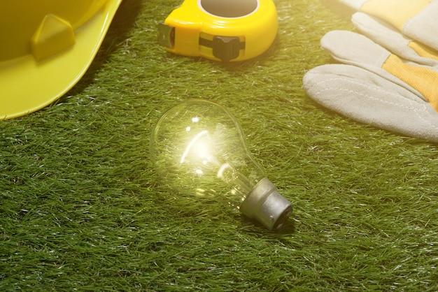Conceito de idéias de engenheiro e arquiteto de casa com lâmpada. chapéu amarelo e ferramentas na grama verde
