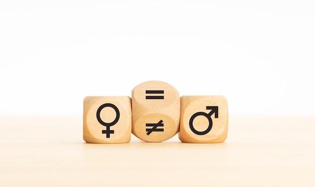 Conceito de igualdade de gênero. bloco de madeira transformando um sinal desigual em um sinal de igual entre os símbolos de homens e mulheres. copie o espaço
