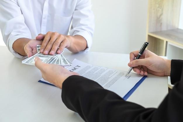 Conceito de ilegal, desonesto, suborno e corrupção, empresário dando dinheiro de suborno no envelope de seu parceiro para dar sucesso ao contrato de negócio em um esquema de corrupção por suborno.