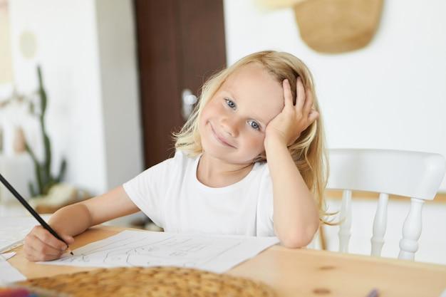 Conceito de imaginação, arte, aprendizagem, lazer e desenvolvimento infantil. garoto loiro branco bonito com sorriso fofo e olhos azuis, segurando um lápis, gostando de desenhar e colorir