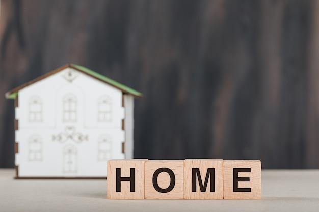 Conceito de imóveis com cubos de madeira, modelo de casa e branco.