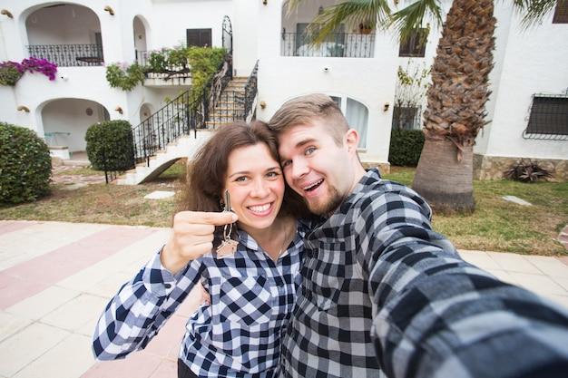 Conceito de imóveis, imóveis e aluguel - jovem casal feliz e sorridente mostrando as chaves de seu novo