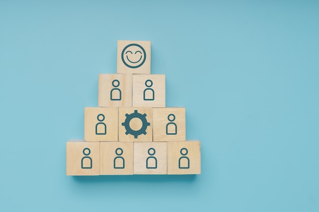 Conceito de implantação e controle de líder ou gerente gentil e profissional, rosto do bloco de madeira de sorriso em cima do ícone de etapa do empresário para o sucesso em fundo azul suave