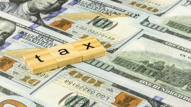 Conceito de imposto com bloco de madeira em notas de dólar.