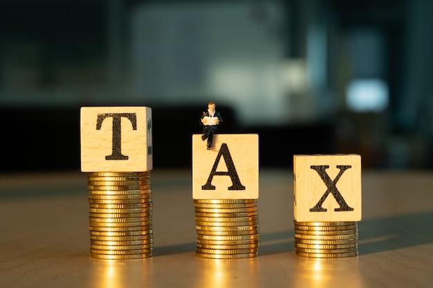 Conceito de imposto. empresário em miniatura e moedas de ouro.