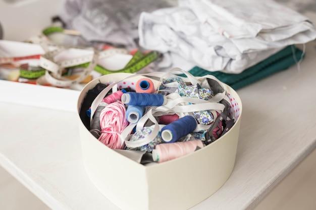 Conceito de indústria e moda - feche o retrato da linha de costura na caixa-coração e os acessórios de costura