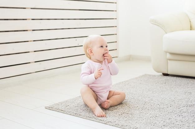 Conceito de infância e crianças - bebê fofo e encantador sentado no chão