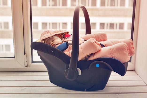 Conceito de infância e segurança - menina bebê dormindo na cadeirinha infantil.