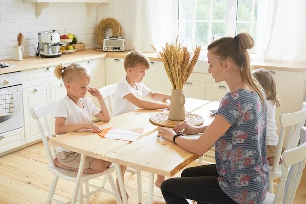 Conceito de infância, família, criatividade, lazer e hobby. foto horizontal de uma jovem mãe vestida de maneira casual passando a licença maternidade com seus três filhos, fazendo artesanato de origami juntos