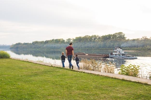 Conceito de infância, família e paternidade - pai e filhos caminhando juntos.