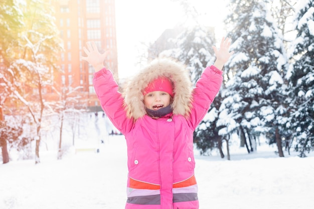 Conceito de infância, moda, temporada e pessoas - 4k menina brincando na neve, inverno, ver criança feliz fazendo bola de neve, par do boneco de neve, crianças nas férias de natal. rosto de garota feliz com roupas de inverno