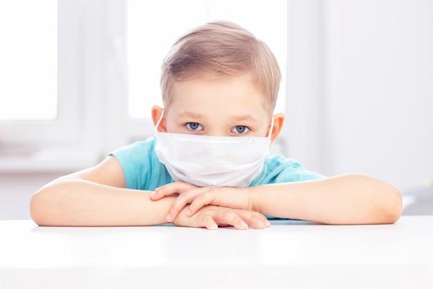 Conceito de infecção por coronavírus. rapaz de máscara médica está sentado em uma cadeira dentro de casa. menino entediado e triste