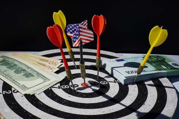Conceito de inflação monetária ou taxa de juros. um alvo com um dardo com a bandeira dos eua, notas de euro e eua em cem dólares ao redor.