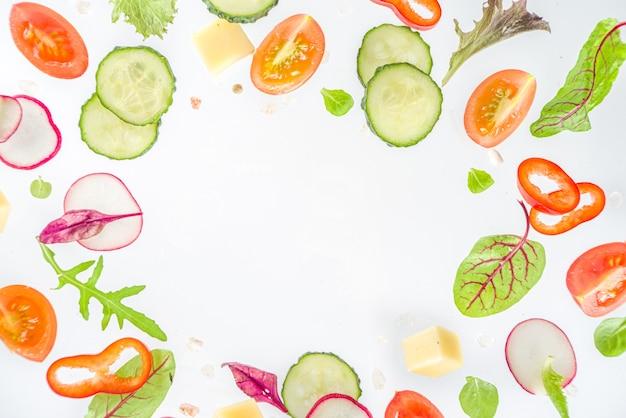 Conceito de ingredientes de salada de primavera. alimentação saudável em fundo branco. legumes, tomates, pimentões, folhas verdes. camada plana, vista superior, espaço de cópia
